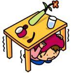 机の下に避難する女性